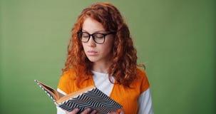 Ritratto di bella ragazza in libro di lettura di vetro su fondo verde stock footage