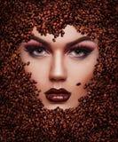 Ritratto di bella ragazza nei chicchi di caffè fotografia stock libera da diritti