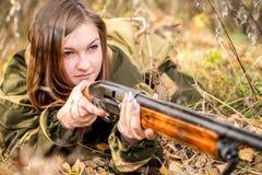 Ritratto di bella ragazza nel cacciatore del cammuffamento con il fucile da caccia Immagine Stock