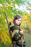Ritratto di bella ragazza nel cacciatore del cammuffamento con il fucile da caccia Fotografia Stock