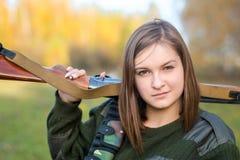 Ritratto di bella ragazza nel cacciatore del cammuffamento con il fucile da caccia Fotografie Stock