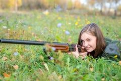 Ritratto di bella ragazza nel cacciatore del cammuffamento con il fucile da caccia Fotografie Stock Libere da Diritti