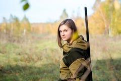 Ritratto di bella ragazza nel cacciatore del cammuffamento con il fucile da caccia Immagini Stock