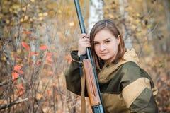 Ritratto di bella ragazza nel cacciatore del cammuffamento con il fucile da caccia Immagine Stock Libera da Diritti