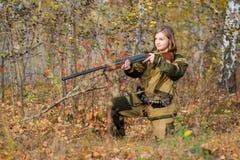 Ritratto di bella ragazza nel cacciatore del cammuffamento con il fucile da caccia Immagini Stock Libere da Diritti