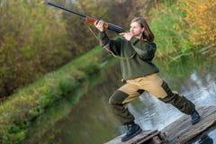 Ritratto di bella ragazza nel cacciatore del cammuffamento con il fucile da caccia su un fondo del fiume Fotografia Stock