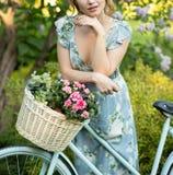 Ritratto di bella ragazza nella foresta, tenente una bici con un canestro dei fiori, dietro i raggi del sole, un blu fiorito fotografia stock libera da diritti