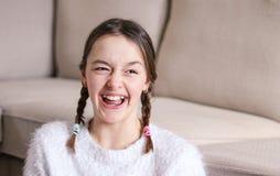 Ritratto di bella ragazza preteen di risata felice con due trecce a casa Giorno degli sciocchi di aprile Emozioni dei bambini fotografia stock