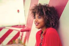 Ritratto di bella ragazza riccia che si appoggia la parete e sorridere fotografia stock