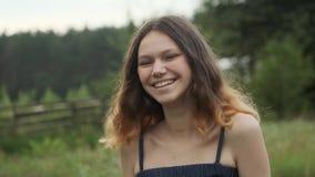 Ritratto di bella ragazza di risata sorridente allegra dell'adolescente 15 anni, con capelli volanti marroni che esaminano macchi stock footage