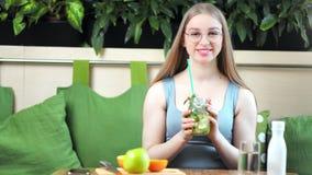 Ritratto di bella ragazza sorridente di forma fisica che beve bevanda sana che posa alla cucina moderna video d archivio