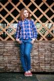 Ritratto di bella ragazza sorridere, posante sulla macchina fotografica in una camicia blu in una gabbia Sulla griglia di legno d Immagine Stock Libera da Diritti