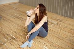 Ritratto di bella ragazza di sport in abiti sportivi variopinti luminosi che riposano dopo un'acqua potabile di allenamento di fo fotografia stock libera da diritti