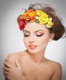 Ritratto di bella ragazza in studio con le rose rosse e gialle nei suoi capelli e spalle nude Giovane donna sexy con trucco Fotografie Stock Libere da Diritti