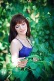Ritratto di bella ragazza su un fondo delle foglie verdi fotografia stock