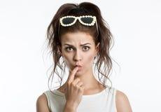 Ritratto di bella ragazza su un fondo leggero Emozioni umane Sorpresa, dubbio, timore fotografia stock