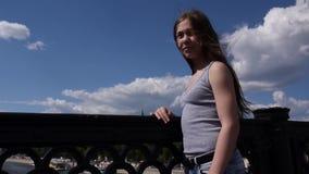 Ritratto di bella ragazza sui precedenti del cielo blu del ponte con capelli di salto in vento stock footage