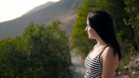 Ritratto di bella ragazza sveglia felice nelle montagne su un fondo di una foresta archivi video