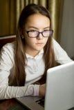Ritratto di bella ragazza teenager in occhiali facendo uso del computer portatile Immagini Stock Libere da Diritti