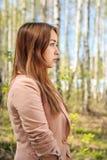 Ritratto di bella ragazza in un boschetto della betulla (nel profilo) fotografia stock