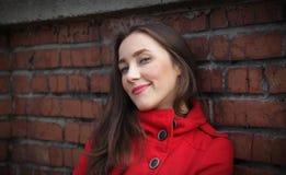Ritratto di bella ragazza in un cappotto rosso su un muro di mattoni fotografia stock