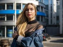 Ritratto di bella ragazza in un rivestimento del denim sui precedenti di un centro di affari moderno un giorno soleggiato luminos fotografie stock