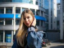 Ritratto di bella ragazza in un rivestimento del denim sui precedenti di un centro di affari moderno un giorno soleggiato luminos immagini stock libere da diritti