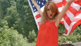 Ritratto di bella ragazza in un vestito rosso contro lo sfondo delle montagne della foresta e del cielo Festa dell'indipendenza d video d archivio