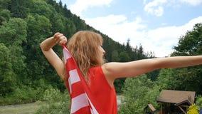 Ritratto di bella ragazza in un vestito rosso contro lo sfondo delle montagne della foresta e del cielo Festa dell'indipendenza d archivi video