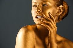 Ritratto di bella signora con la pittura dell'oro su pelle contro fondo grigio immagine stock libera da diritti