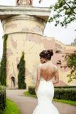 Ritratto di bella sposa castana felice in vestito bianco da nozze che si tiene per mano nel mazzo dei fiori all'aperto Immagine Stock