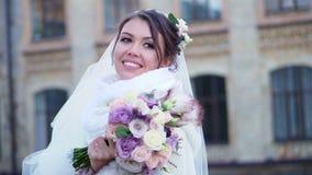 Ritratto di bella sposa, in un vestito, in un velo ed in una pelliccia bianchi la sposa sta sorridendo felicemente, tenendo un ma stock footage