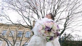 Ritratto di bella sposa, in un vestito, in un velo ed in una pelliccia bianchi tenuta del mazzo di nozze Contro lo sfondo di archivi video
