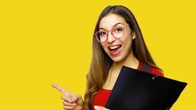 Ritratto di bella studentessa lunga dei capelli che indossa i vetri rossi del nerd e della maglietta, indicante con il dito indic fotografia stock