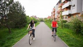 Ritratto di belle coppie attraenti in bici retro delle attrezzature di guida globale casuale dei jeans che godono del riciclaggio stock footage