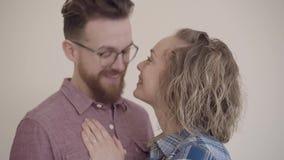 Ritratto di belle coppie che baciano sulla fine beige del fondo su Uomo barbuto in anello di tocco di vetro sulla mano della mogl archivi video