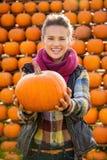 Ritratto di belle zucche sorridenti della tenuta della donna sull'azienda agricola Fotografie Stock