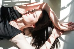 Ritratto di bellezza del fronte femminile con pelle naturale, donna che mette su fondo soleggiato bianco in biancheria intima ner fotografia stock