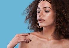 Ritratto di bellezza della ragazza con l'acconciatura di afro Ragazza che posa sul fondo blu Colpo dello studio Fotografia Stock