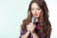 Ritratto di bello cantante elegante della ragazza castana con capelli lunghi con un microfono in sua mano che canta una canzone Fotografie Stock Libere da Diritti