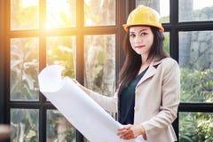 Ritratto di bello costruttore asiatico dell'architetto della donna con giallo Immagine Stock
