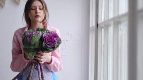 Ritratto di bello fiorista con un mazzo viola dei fiori insoliti - brassica guardi nella macchina fotografica archivi video