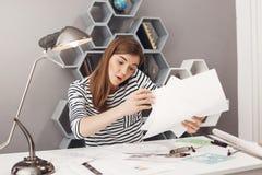 Ritratto di bello giovane progettista indipendente femminile europeo concentrato moro che parla sul telefono con il gruppo Fotografia Stock