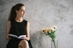 Ritratto di bello libro di lettura della giovane donna che si rilassa nel salone immagini d'annata di stile di effetto Fotografia Stock