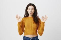 Ritratto di bello modello femminile sexy che mostra i segni fini e che dice okay mentre gray eccessivo calmo e serio diritto Fotografie Stock Libere da Diritti