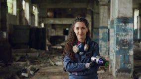 Ritratto di bello pittore sorridente dei graffiti della ragazza che sta nella nel vecchi costruzione, pitture di spruzzo della te video d archivio