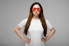 Ritratto di bello riuscito emozionale più il modello di dimensione in occhiali da sole che stanno nello studio che guarda in came immagine stock