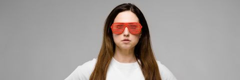 Ritratto di bello riuscito emozionale più il modello di dimensione in occhiali da sole che stanno nello studio che guarda in came immagine stock libera da diritti