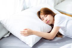 Ritratto di bello sonno asiatico della giovane donna che si trova a letto con la testa sul cuscino comodo e soddisfatto di svago fotografia stock libera da diritti
