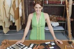 Ritratto di bello stilista femminile che sta alla tavola con le disposizioni Fotografie Stock